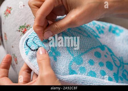 Woman sews up clothes. Hands seamstress close-up. Mending clothes. - Stock Photo