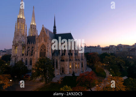 Vienna panorama at sunset. Autumn colors, neogothic church Votivkirche in the foreground. - Stock Photo