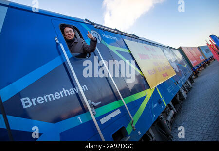 12 November 2019, Mecklenburg-Western Pomerania, Sassnitz: Dong Wanxu, CEO of Beijing Trans Eurasia International Logistics, is waving from the locomotive of the first container train, which, as part of the Chinese Silk Road Initiative, will travel to the loading quay in the port of Mukran on the island of Rügen. For the first time on the entire route between Germany and China, part of the journey will be by sea between the ports of Mukran and Baltysk in the Kaliningrad region. A ship with the first 41 containers of a test train, which had started at the beginning of November in Xi'an in centr - Stock Photo