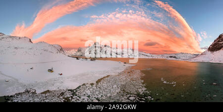 Aerial drone panorama photo. Beautiful sunset over the mountains and sea of the Lofoten Islands. Reine, Norway. Winter landscape with amazing colors.