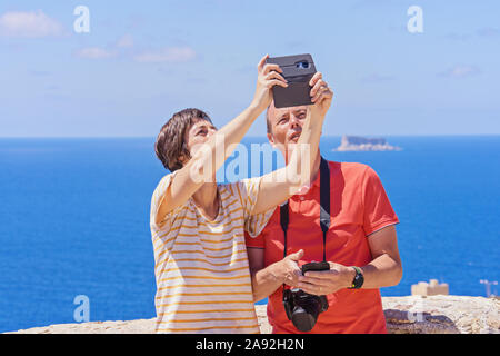 Caucasian white middle-aged couple people take selfie using mobile phone outdoor. Summer traveling concept: Zurrieq, Malta - May 1, 2019 - Stock Photo