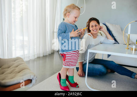 Mother with daughter using cell phone