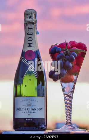 Bottle of champagne and glass of champagne with grapes and fruit against sunset sky - Stock Photo