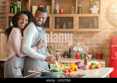 Thankful wife hugging her husband from behind at kitchen - Stock Photo