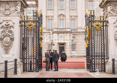 Looking through open front gates of Buckingham Palace, central London, UK. Armed police on guard checking security of visitors. Guarding royal family. - Stock Photo
