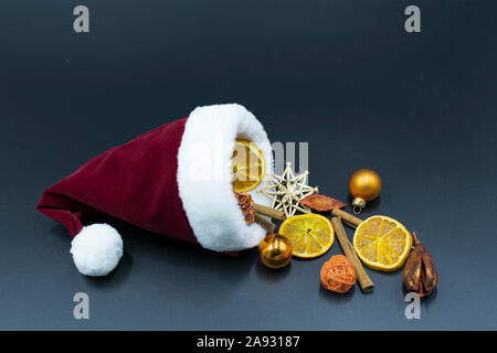 Santa hat with Christmas decorations made of cinnamon sticks, dried orange slices and Christmas tree ornaments on dark background - Stock Photo