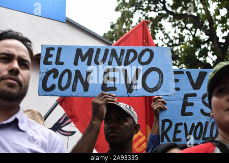 A man holding a placard that reads 'The World With Evo' during the protest.Supporters of social movements and Venezuelan communist youth protest in support of former president, Evo Morales in front of the Bolivian embassy. The president of the country resigned after strong protests against his re-election and for refusing to conduct an audit of votes. - Stock Photo
