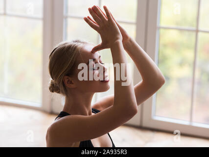Portrait of peaceful girl practicing yoga at home