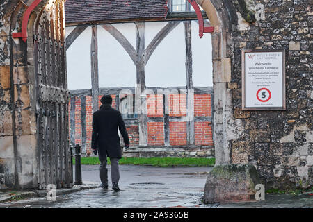 Welcome sign on a stone wall at an entrance to the precincts of Winchester cathedral, England. - Stock Photo
