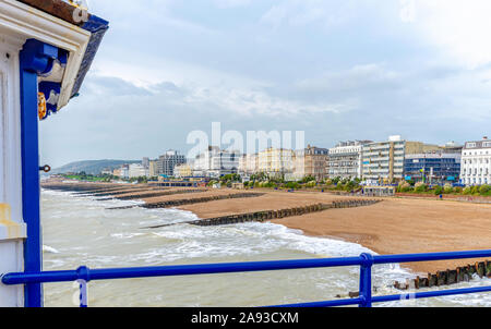 Panorama of the beach and front at Eastbourne.  A handrail and side of a kiosk is in the foreground and hotels line the seafront. A cloudy sky is abov - Stock Photo