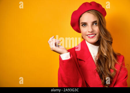 A beautiful girl with red lips stands in a red coat and takes on a yellow background and wets frame. - Stock Photo