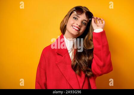 A beautiful girl with red lips stands in a red coat on a yellow background and looks up at the frame, lifting her sunglasses. - Stock Photo