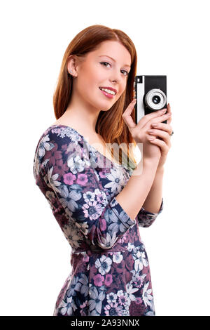 Side portrait of a fashionable, beautiful smiling young girl taking a photo with an old film vintage camera, isolated on white background. - Stock Photo