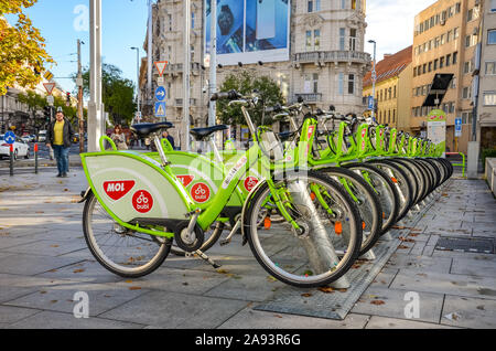 Budapest, Hungary - Nov 6, 2019: Public green bikes for rental in the center of the Hungarian capital. Bike sharing. Eco-friendly means of transport. Ecological measure in the cities. Bicycles. - Stock Photo