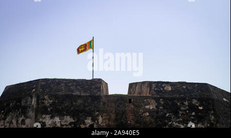 GALLE, SRI LANKA - AUGUST 10, 2016:  The best city of south of Sri Lanka, The Old Clock Tower and the Sri Lanak flag At Galle Dutch Fort 17th Centurys - Stock Photo