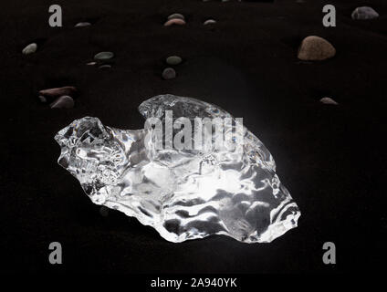 Glistening chunks of ice wash up on a lava black sand beach in the North Atlantic, giving the appearance of diamonds on the beach at Jokulsarlon glaci - Stock Photo
