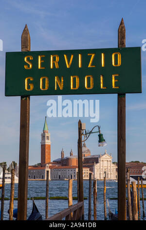 Venice, Italy - July 17th 2019: A view through a Servizio Gondole sign on the main island in Venice, Italy, with the view of the island of San Giorgio - Stock Photo