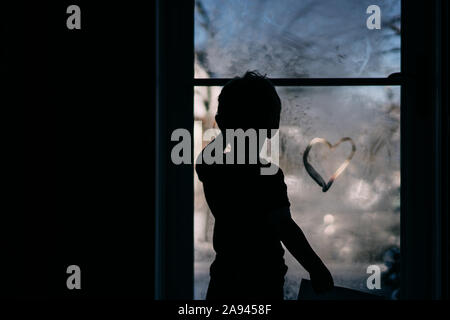 A little boy draws a heart on a foggy storm door. - Stock Photo