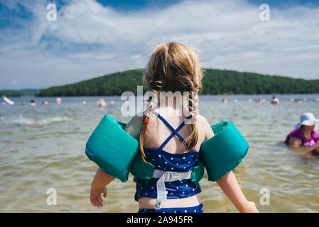 A little girl wearing a floatation device looks out at the lake. - Stock Photo