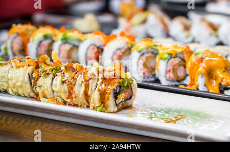 Plates with various kinds of expertly cooked and sliced sushi with spices and hot sauces are displayed on dining table to enjoy delicious and dietary
