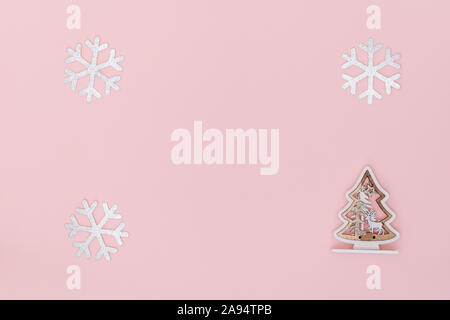 New Year and Christmas composition. Frame from snowflakes, chrismas tree on pastel pink paper background. Top view, flat lay, copy space. - Stock Photo