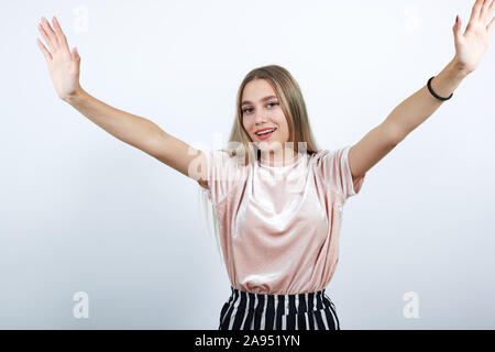 Attractive young woman spreading hands, and looking so funny, pretty - Stock Photo