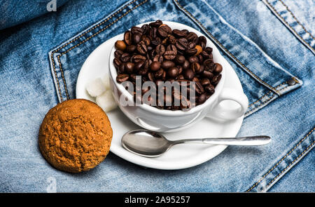 Cup with coffee beans, refined sugar and spoon on plate, denim background. Coffee break concept. Mug full of coffee beans and oat cookie on jeans. - Stock Photo