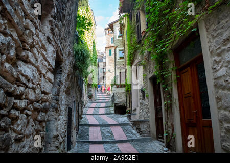 Tourists including a young couple walk up the narrow street path in the medieval village of Dolceacqua, Italy - Stock Photo