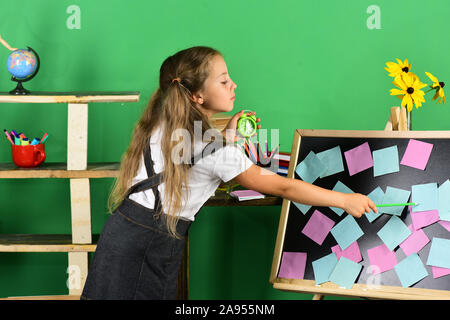 Kid and school supplies on green wall background. Back to school and childhood concept. Girl with ponytails point at sticky notes on blackboard. Schoolgirl with serious face holds green alarm clock - Stock Photo