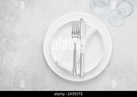 Restaurant table setting with white plates, glasses and cutlery. Light gray background with copy space. Overhead shot. - Stock Photo