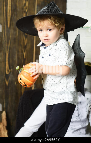 Kid with scared faces in witch hats plays with carved pumpkins. Halloween and holiday concept. Little magician makes Halloween decor. Boy on wooden and white background - Stock Photo