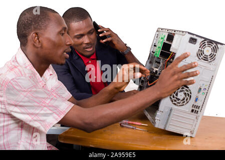 two technicians sitting at the desk working together on a computer - Stock Photo