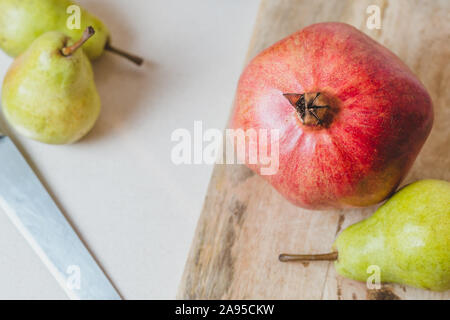 Fresh pears and pomegranates in the kitchen on a cutting wooden board - home cooking - Stock Photo