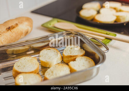 Closeup of housewife fry baguette pieces in a frying pan - making crispy sandwiches - Stock Photo