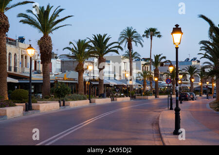 Rethymno, Crete, Greece. View along the illuminated palm-lined seafront promenade, dawn.