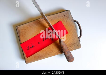 Closeup and focus on the phrase make a killing written on red paper, stuck to the cutting board with rusty chopping knife, on white wooden surface - Stock Photo