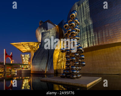Sculpture 80 Balls Stainless steel by Anish Kapoor outside the illuminated Guggenheim Museum at evening, Nervión River, Bilbao, Basque Country, Spain - Stock Photo