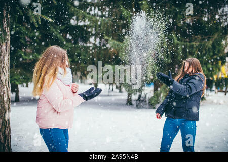 On a good winter day, two friends play snowballs in a clearing in the park between the trees - Stock Photo