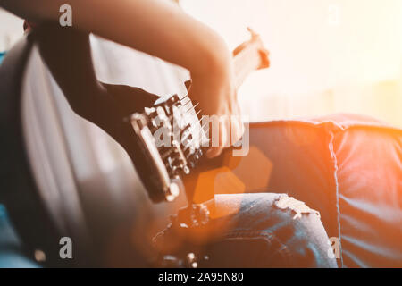 Closeup of a child playing a black electric guitar - the hand hits the strings