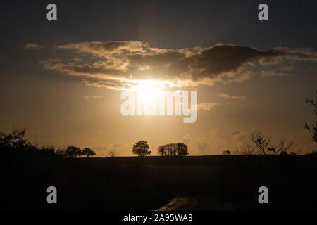 The sun setting over the fields looking towards bodmin moor near the village of Stoke Climsland, Cornwall, England. - Stock Photo