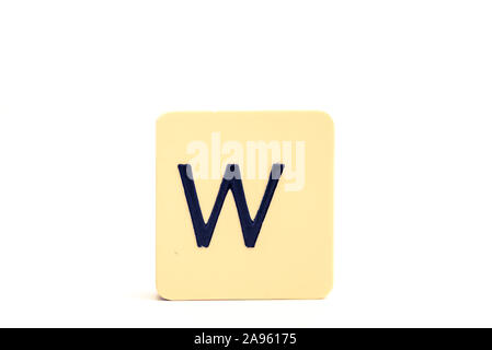 Dark letter W on a pale yellow square block isolated on white background - Stock Photo