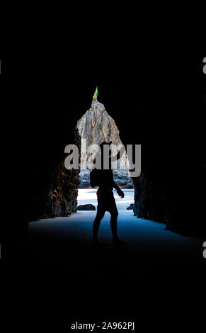 Silhouette of a man against the light coming outside a cave