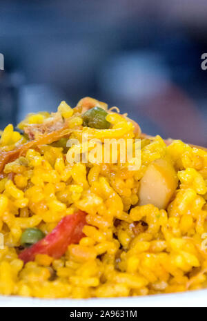 Paella served on a plate surrounded by blurred background - Stock Photo
