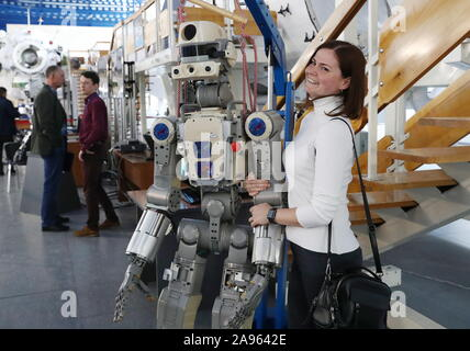 Zvyozdny Gorodok, Russia. 13th Nov 2019. A visitor poses with the humanoid robot Fedor (Skybot F-850) for a photograph at the 13th Manned Space Flights international conference at Yuri Gagarin State Scientific Research-and-Testing Cosmonaut Training Center (GCTC) in Zvyozdny Gorodok , Moscow Region, Russia; the conference is organised biannually by Gagarin Cosmonaut Training Center with the support of Roscosmos Corporation to discuss manned spacecraft operation, the selection and training of cosmonauts (astronauts), in-flight activities and post-flight rehabilitation. Credit: ITAR-TASS News Ag - Stock Photo