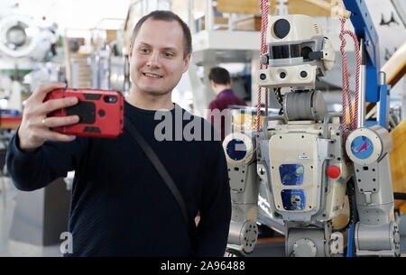 Zvyozdny Gorodok, Russia. 13th Nov 2019. A visitor takes a selfie with the humanoid robot Fedor (Skybot F-850) at the 13th Manned Space Flights international conference at Yuri Gagarin State Scientific Research-and-Testing Cosmonaut Training Center (GCTC) in Zvyozdny Gorodok , Moscow Region, Russia; the conference is organised biannually by Gagarin Cosmonaut Training Center with the support of Roscosmos Corporation to discuss manned spacecraft operation, the selection and training of cosmonauts (astronauts), in-flight activities and post-flight rehabilitation. Credit: TASS/Alamy Live News - Stock Photo