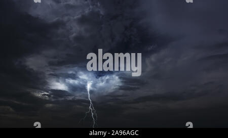 Thunderstorm clouds at night with lightning. Evening thunderstorm landscape background. Impressive lightning storm sky. Stock Photo