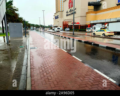 Dubai / UAE - November 10, 2019: Cars driving through the flooded streets in Dubai during rain. Heavy rain in UAE and puddles. Rainy in desert - Stock Photo