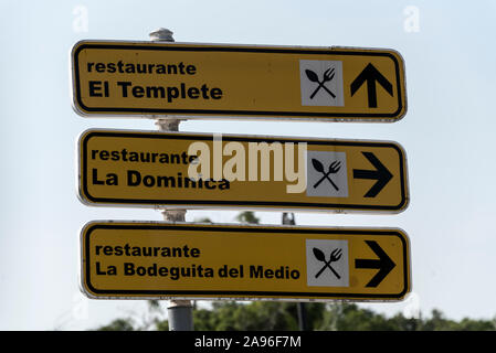 A road direction sign indicating the locations of restaurants in Havana, Cuba - Stock Photo