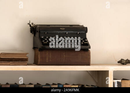 The American author, Ernest Hemingway's type writer placed on top of a thick book on a bookshelf at his home, Finca La Vigia, in San Francisco de Paul - Stock Photo