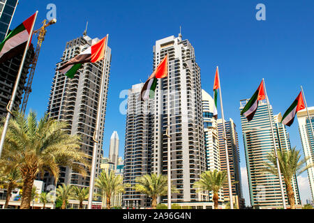 Dubai / UAE - November 11, 2019: View of JLT skyscrapers with UAE flags. United Arab Emirates flags waving on blue sky background. National day. Group - Stock Photo